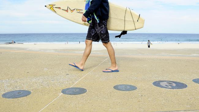 A surfer walks past the Surfing Walk of Fame at Maroubra. Picture: John Appleyard